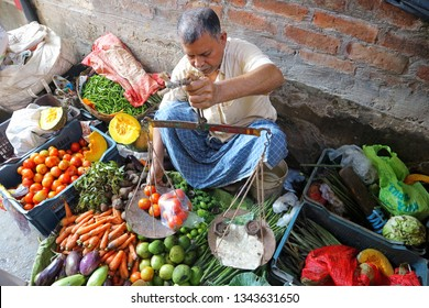 A senior Indian citizen trades vegetables in the market. A man weighs tomatoes on hand weights. Nabadwip, India, March 18, 2019.