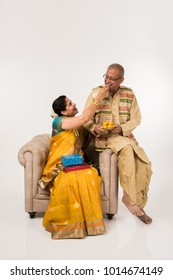 Senior indian couple in traditional Indian wear sitting on sofa and eating sweets