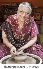 senior Indian female potter shaping up the pot on wheal