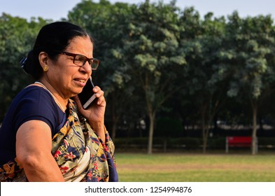 Senior Indian woman speaking on phone, sitting in a park in New Delhi, India