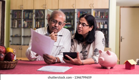 Senior Indian/asian couple accounting, doing home finance and checking bills with laptop, calculator and money while sitting on sofa/couch or dining table at home