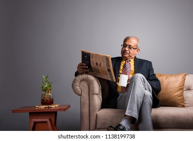 Senior Indian/asian executive or businessman in suit and tie, reading news in newspaper or on smartphone while sitting on sofa or couch with a coffee mug