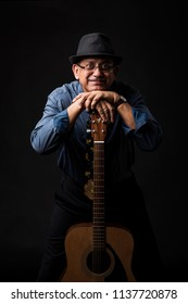 senior Indian/asian handsome man playing or posing with musical string instrument like guitar or violin, standing over black background or sitting on sofa/couch