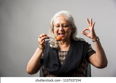 Senior Indian/asian lady eating sweet Gulab Jamun with spoon