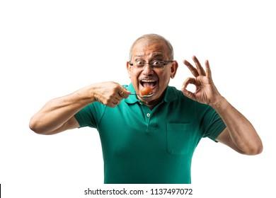 Senior Indian/asian man eating sweet Gulab Jamun with spoon