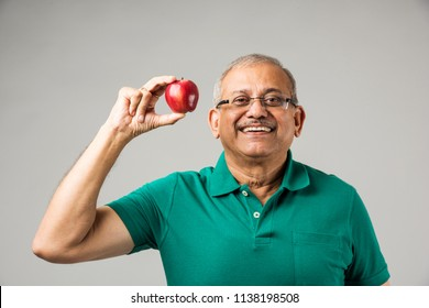senior Indian/asian man holding fresh apple. Old age and oral health concept