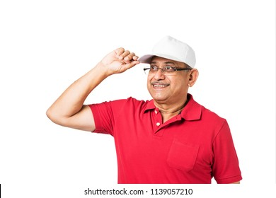 senior indian/asian man wearing and adjusting a white sports cap, standing isolated over white background