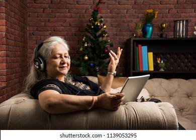 senior Indian/asian women listening to music using headphones while holding a tablet computer and sitting on sofa or couch at home