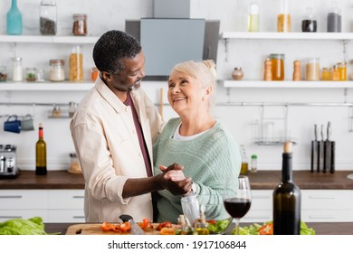senior interracial husband and wife smiling while holding hands in kitchen
