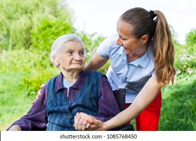 Senior invalid woman spending time outdoor with friendly young caregiver