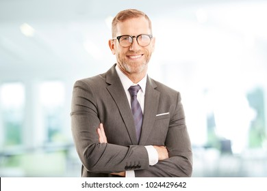 Senior investment advisor businessman with folded arms wearing suit while standing at the office and looking at camera.