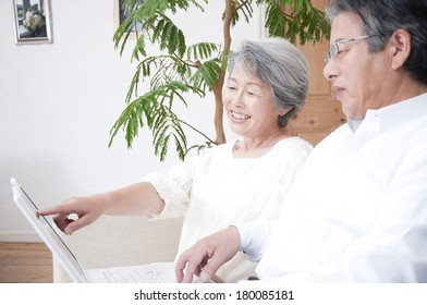 Senior Japanese couple smiling and looking at a laptop