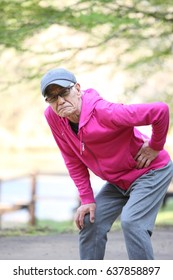 Senior Japanese man with flank pain during jogging