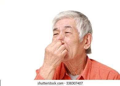 senior Japanese man holding his nose