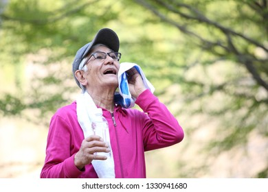 Senior Japanese man in a hoodie after exercise wiping off sweat outside