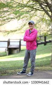 senior Japanese man in a hoodie smiles outdoor