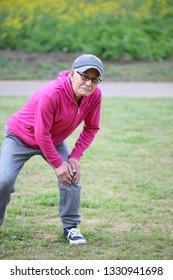 Senior Japanese man with knee pain during workout