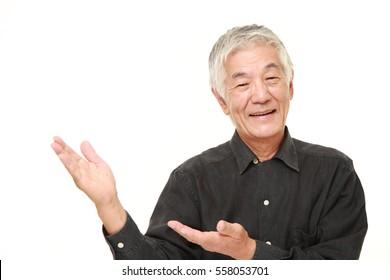 senior Japanese man presenting and showing something
