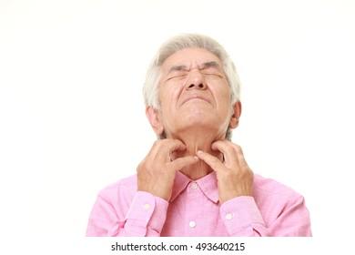 senior Japanese man scratching his neck