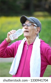 senior Japanese man sweaty and thirsty after exercise drinks water outside