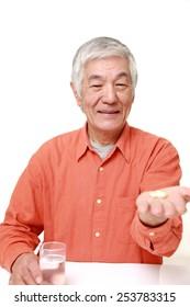 senior Japanese man takes a supplement