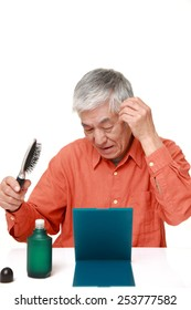 senior Japanese man using hair restorer