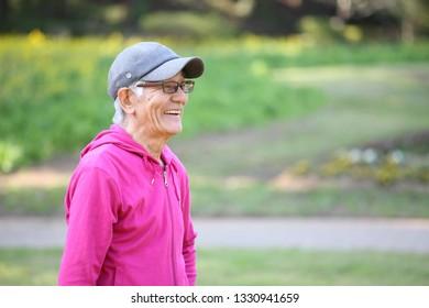 senior Japanese man wearing pink parka smiles outdoor