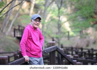 senior Japanese man wearing pink parka standing on the wooden deck at natural park