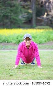senior Japanese man wearing pink parka doing push up on a lawn