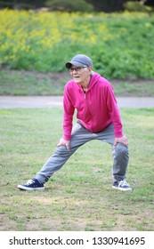 senior Japanese man wearing pink parka doing leg stretch outdoor