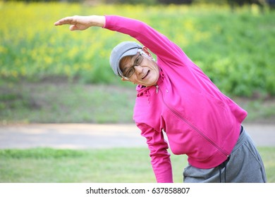 senior Japanese man wearing pink parka doing standing side bend exercise