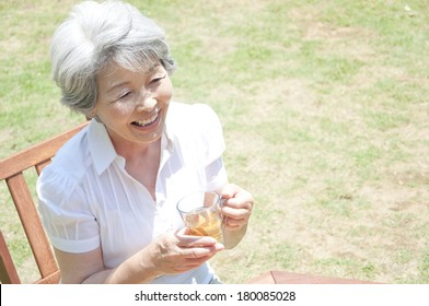 A senior Japanese woman laughs as she takes tea in the garden