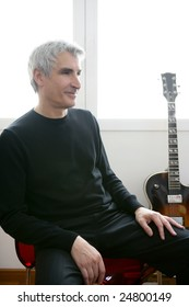 Senior jazz musician portrait, with his guitar in background