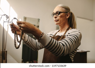 Senior jewelry maker hanging a necklace on stand. Mature female goldsmith working at her workshop.