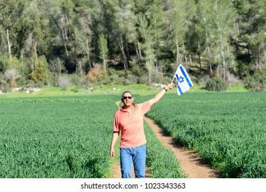 Senior jewish man holding Israeli flag, walking on nature background.Memorial day-Yom Hazikaron, Patriotic holiday  Independence day Israel - Yom Ha'atzmaut concept.