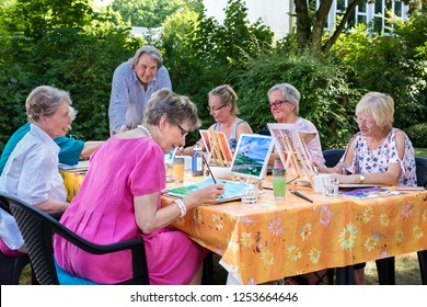 Senior ladies taking art lessons  sitting outdoors at the table and painting pictures, following male instructors.