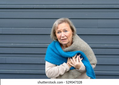 Senior lady clutching her chest in pain at the first signs of angina or a myocardial infarct or heart attack, upper body on grey metal door background with copy space