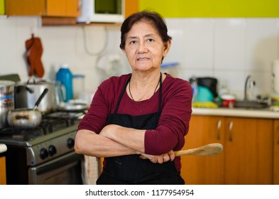 Senior lady cook from home holding a wooden spoon, concept of housewife or home cooking