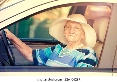 senior lady in glasses driving automobile