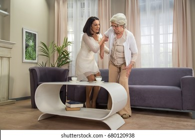 Senior lady with hip problem stand up with assistance from adult female