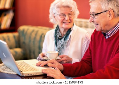 Senior lady holding a cup of tea while her partner looks at his laptop