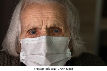 Senior lady with hygienic facial mask. Old woman with frightened eyes. COVID-19 concept, social distance