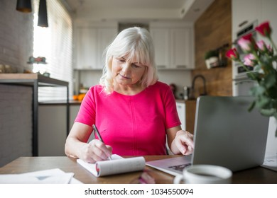 Senior lady at kitchen table taking notes using notebook