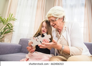 Senior lady and little girl are playing puzzle game