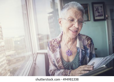 Senior lady looking at old photographs in an album, remembering her past