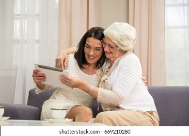 Senior lady and middle aged female interacting with a tablet