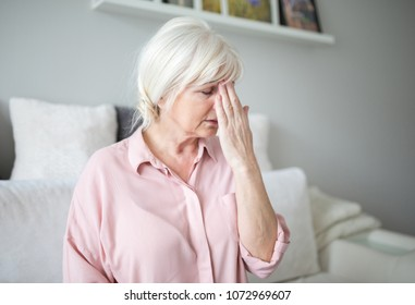 Senior lady with migraine touching her forehead