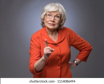 Senior lady points finger up on gray background with copy space