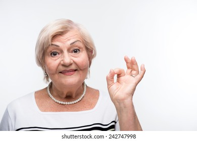 Senior lady satisfied. Closeup portrait of active elderly woman smiling and showing OK sign while standing against white background