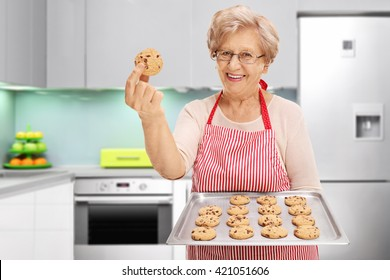 Senior lady showing her homemade chocolate chip cookies in a kitchen